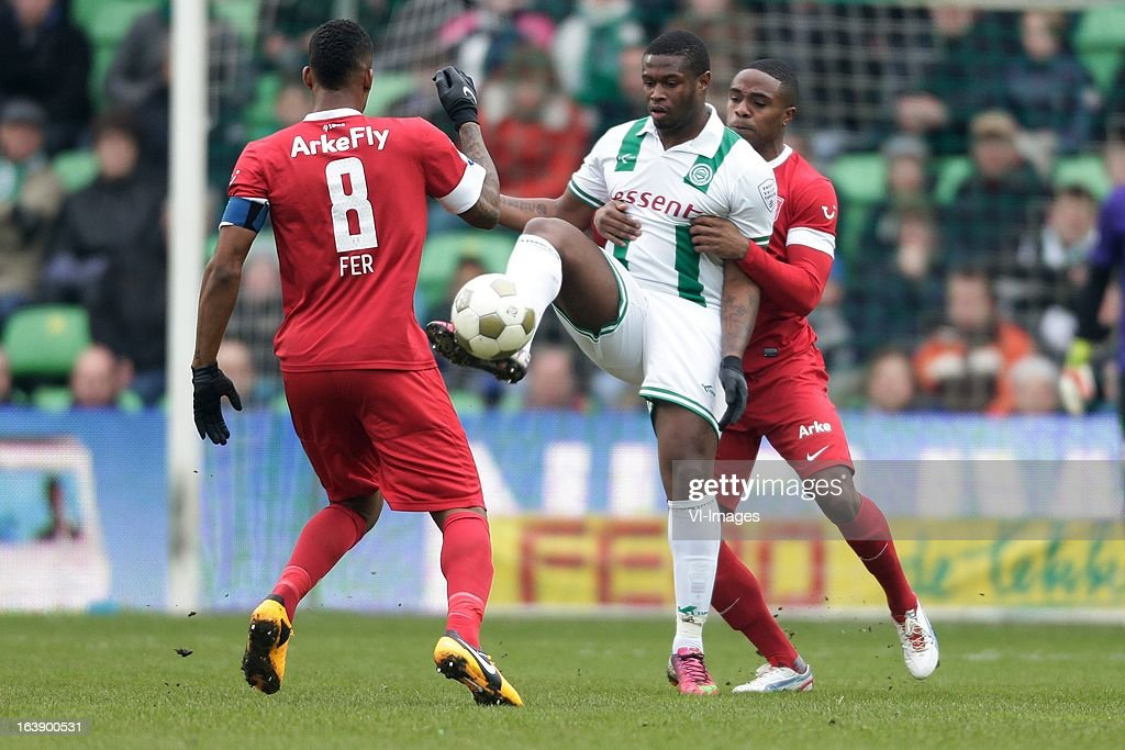 Edson Braafheid (R) Leroy Fer (L) of FC Twente Genero Zeefuik of FC Groningen (C) during the Dutch Eredivisie match between FC Groningen and FC Twente at the Euroborg Stadium on march 17, 2013 in Groningen, The Netherlands