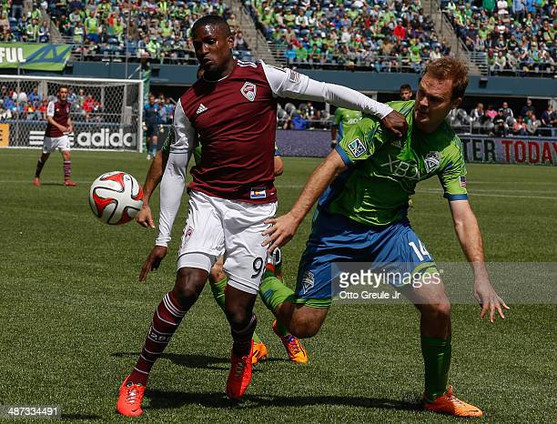Edson Buddle of the Colorado Rapids dribbles against Chad Marshall of the Seattle Sounders FC at CenturyLink Field on April 26 2014 in Seattle...