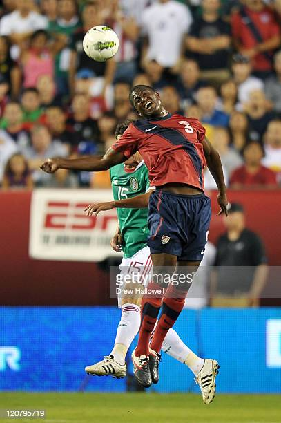 Edson Buddle of the United States heads the ball in front of Hector Moreno of Mexico at Lincoln Financial Field on August 10 2011 in Philadelphia...