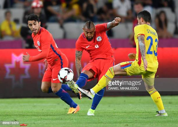 Edson Puch and Arturo Vidal of Chile vie for the ball with Nicolae Stanciu of Romania during their international friendly football matchbetween...