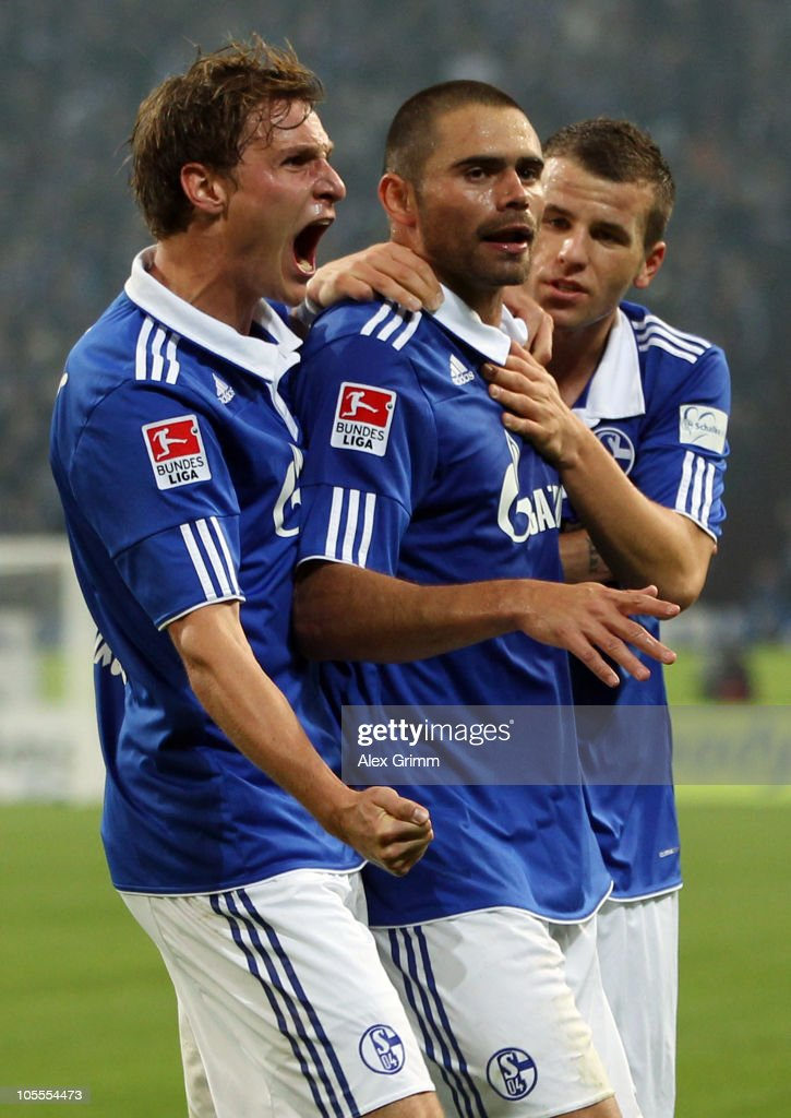 Edu (C) of Schalke celebrates his team's first goal with team mates <a gi-track='captionPersonalityLinkClicked' href=/galleries/search?phrase=Benedikt+Hoewedes&family=editorial&specificpeople=3945465 ng-click='$event.stopPropagation()'>Benedikt Hoewedes</a> (L) and <a gi-track='captionPersonalityLinkClicked' href=/galleries/search?phrase=Lukas+Schmitz&family=editorial&specificpeople=6269299 ng-click='$event.stopPropagation()'>Lukas Schmitz</a> (R) during the Bundesliga match between FC Schalke 04 and VfB Stuttgart at the Veltins Arena on October 16, 2010 in Gelsenkirchen, Germany.