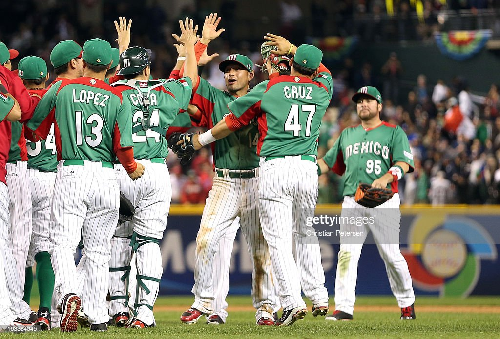 Eduardo Arredondo #14 (C) and Luis Cruz #47 of Mexico celebrate with their teammates after they won 5-2 against the United States during the World Baseball Classic First Round Group D game at Chase Field on March 8, 2013 in Phoenix, Arizona.