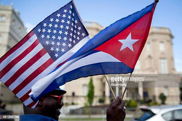 Eduardo Clark holds American and Cuban flags across the street from the Cuban embassy in Washington DC US on Monday July 20 2015 A diplomatic freeze...