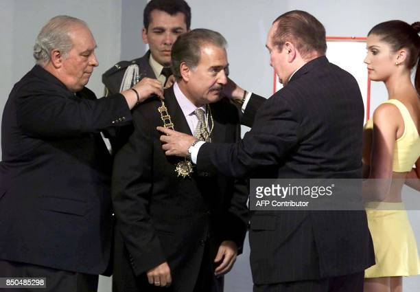 Eduardo Deluca and Nicolas Leoz members of the South American Soccer Confederation decorate Colombian President Andres Pastrana during the drawing of...