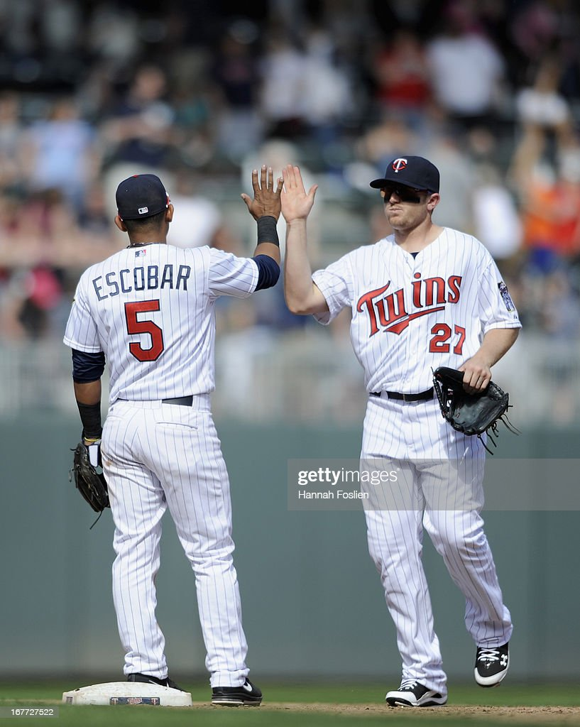 Eduardo Escobar #5 and Chris Parmelee #27 of the Minnesota Twins celebrate a win of the game against the Texas Rangers on April 28, 2013 at Target Field in Minneapolis, Minnesota. The Twins defeated the Ranger 5-0.