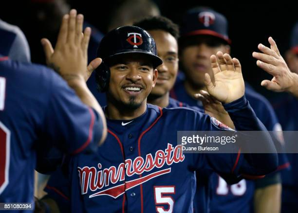 Eduardo Escobar of the Minnesota Twins celebrates in the dugout after scoring against the Detroit Tigers on a single by Byron Buxton during the...