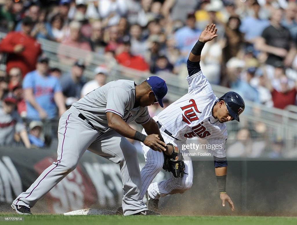 <a gi-track='captionPersonalityLinkClicked' href=/galleries/search?phrase=Eduardo+Escobar&family=editorial&specificpeople=7522733 ng-click='$event.stopPropagation()'>Eduardo Escobar</a> #5 of the Minnesota Twins is safe at third base as <a gi-track='captionPersonalityLinkClicked' href=/galleries/search?phrase=Adrian+Beltre&family=editorial&specificpeople=202631 ng-click='$event.stopPropagation()'>Adrian Beltre</a> #29 of the Texas Rangers applies a tag during the seventh inning of the game on April 28, 2013 at Target Field in Minneapolis, Minnesota. The Twins defeated the Ranger 5-0.