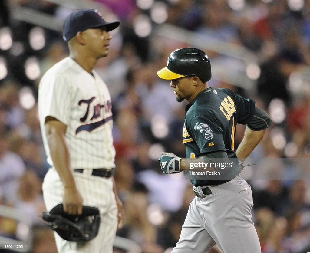 <a gi-track='captionPersonalityLinkClicked' href=/galleries/search?phrase=Eduardo+Escobar&family=editorial&specificpeople=7522733 ng-click='$event.stopPropagation()'>Eduardo Escobar</a> #5 of the Minnesota Twins looks on as <a gi-track='captionPersonalityLinkClicked' href=/galleries/search?phrase=Coco+Crisp&family=editorial&specificpeople=206376 ng-click='$event.stopPropagation()'>Coco Crisp</a> #4 of the Oakland Athletics rounds the bases after solo home run during the third inning of the game on September 11, 2013 at Target Field in Minneapolis, Minnesota.