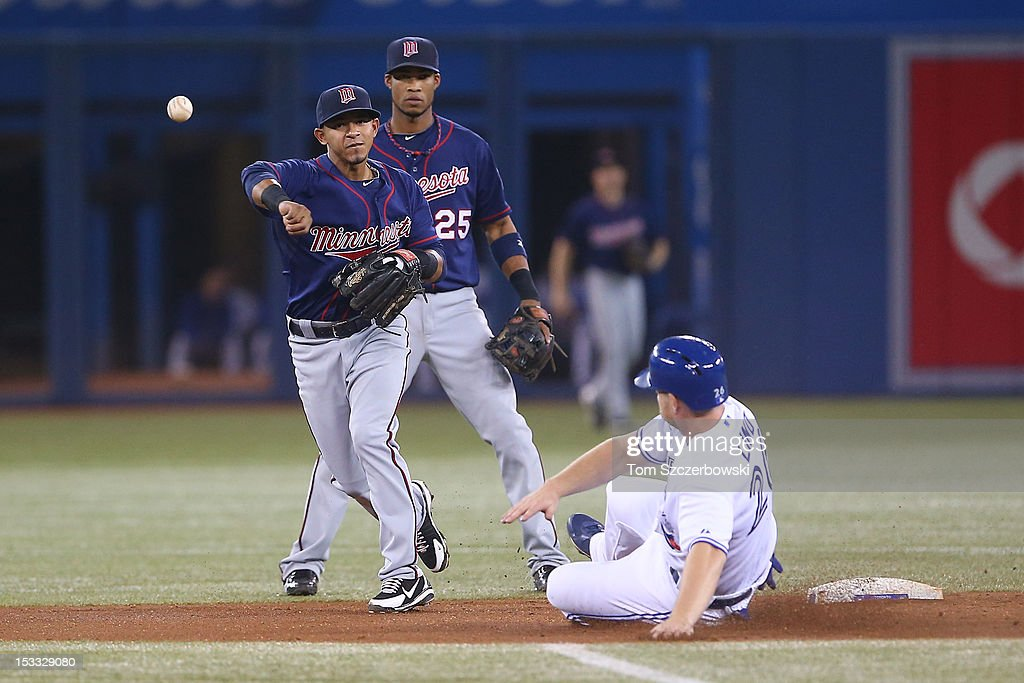 Eduardo Escobar #5 of the Minnesota Twins turns a double play in the second inning as Pedro Florimon #25 watches during MLB game action as <a gi-track='captionPersonalityLinkClicked' href=/galleries/search?phrase=Adam+Lind&family=editorial&specificpeople=3911783 ng-click='$event.stopPropagation()'>Adam Lind</a> #26 of the Toronto Blue Jays slides on October 3, 2012 at Rogers Centre in Toronto, Ontario, Canada.