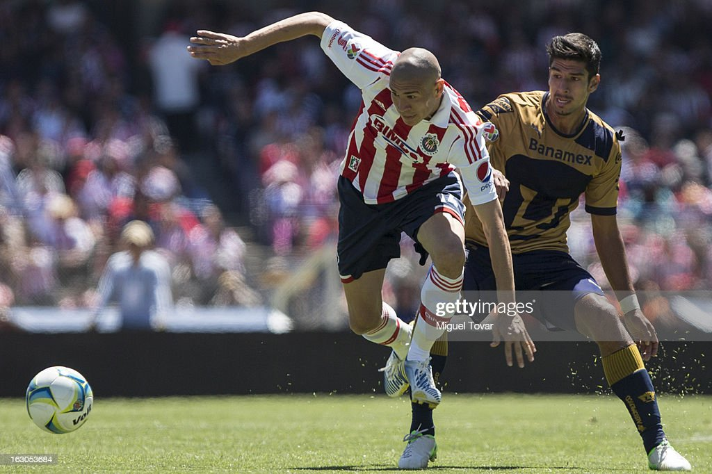 Eduardo Herrera of Pumas fights for the ball with <a gi-track='captionPersonalityLinkClicked' href=/galleries/search?phrase=Jorge+Enriquez&family=editorial&specificpeople=6623957 ng-click='$event.stopPropagation()'>Jorge Enriquez</a> of Chivas during a match between Pumas and Chivas as part of the Clausura 2013 at Olympic stadium on March 03, 2013 in Mexico City, Mexico.