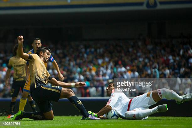 Eduardo Herrera of Pumas fights for the ball with Nahuel Guzman goalkeeper of Tigres during a 10th round match between Pumas UNAM and Tigres UANL as...