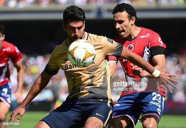Eduardo Herrera of Pumas is challenged by Leobardo Lopez of Veracruz during their Mexican Apertura football tournament quarterfinal match at the...