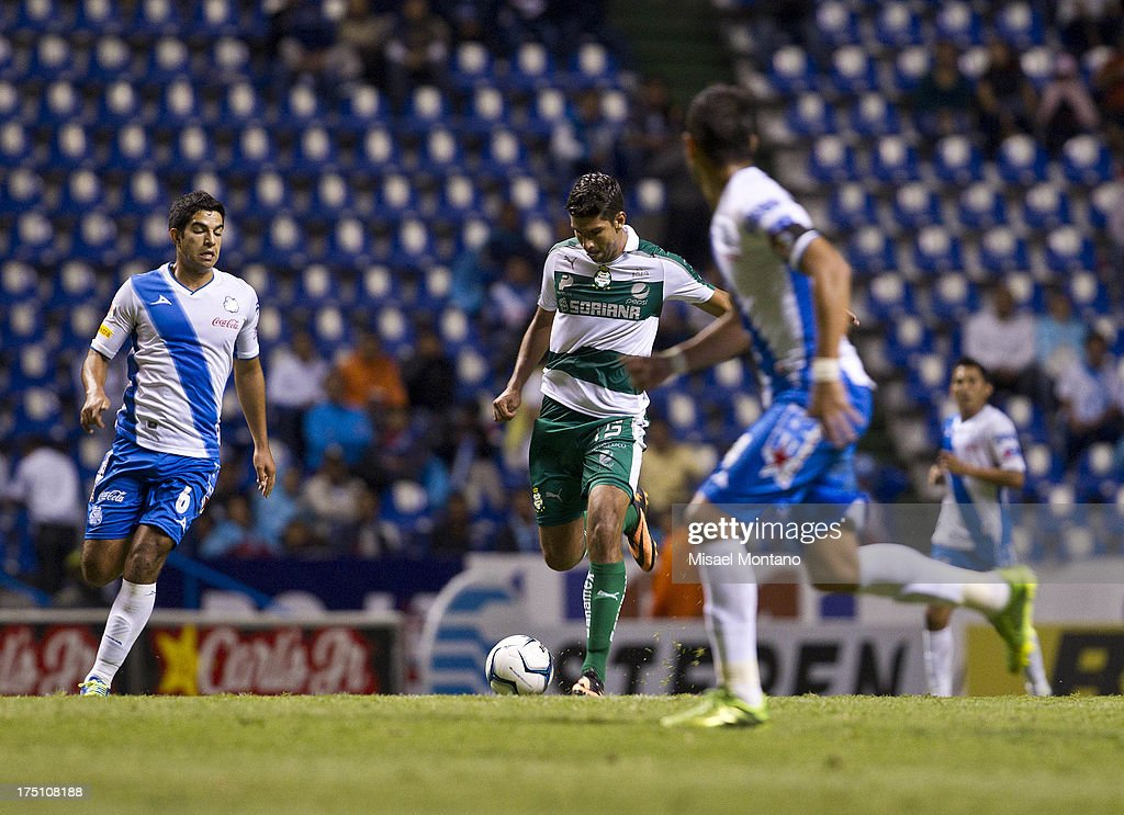 Eduardo Herrera of Santos competes for the ball with Mario Ortiz of Puebla during a match between Puebla and Santos as part of the Torneo de Apertura 2013 Liga MX Championship at Cuauhtemoc Stadium, on July 31, 2013 in Puebla, Mexico.