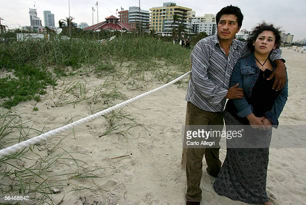 Eduardo Koana and girlfriend Lorena Hernandez stand on the beach shortly after a Chalk's Seaplane burst into flames and plunged into the Atlantic...