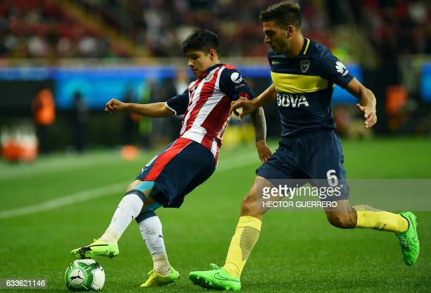 Eduardo Lopez of Guadalajara vies for the ball with Lisandro Magallan of Argentine club Boca Jr during a friendly football match at Chivas stadium on...