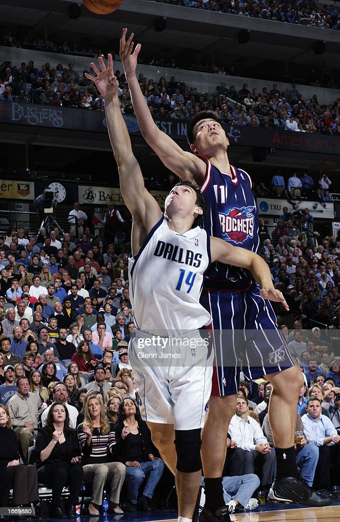 Eduardo Najera #14 of the Dallas Mavericks and Yao Ming #11 of the Houston Rockets battle for the rebound during the NBA game at American Airlines Center on November 21, 2002 in Dallas, Texas. The Mavericks won 103-90.