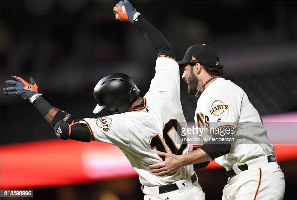 Eduardo Nunez and George Kontos of the San Francisco Giants celebrate after Nunez hit a walkoff RBI single to defeat the Cleveland Indians 21 in the...