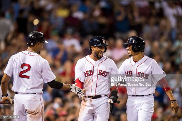 Eduardo Nunez and Mookie Betts of the Boston Red Sox high five Xander Bogaerts after scoring during the fourth inning of a game against the St Louis...