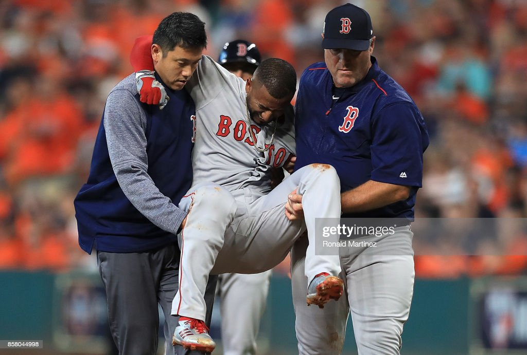 Eduardo Nunez #36 of the Boston Red Sox is carried off the field by Red Sox trainer Masai Takahashi and manager John Farrell after suffering an injury in the first inning against the Houston Astros during game one of the American League Division Series at Minute Maid Park on October 5, 2017 in Houston, Texas.