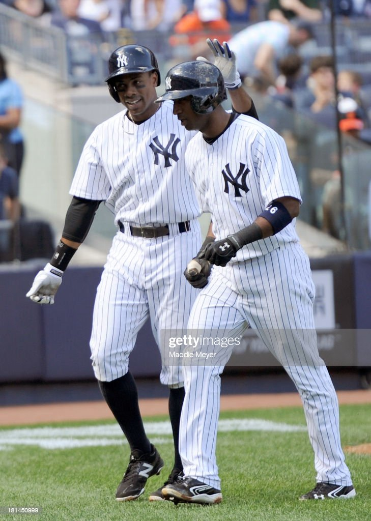 <a gi-track='captionPersonalityLinkClicked' href=/galleries/search?phrase=Eduardo+Nunez&family=editorial&specificpeople=4900197 ng-click='$event.stopPropagation()'>Eduardo Nunez</a> #26 of the New York Yankees celebrates with his teammate <a gi-track='captionPersonalityLinkClicked' href=/galleries/search?phrase=Curtis+Granderson&family=editorial&specificpeople=546997 ng-click='$event.stopPropagation()'>Curtis Granderson</a> #14 after hitting a two-run homer during the fourth inning against the San Francisco Giants during interleague play on September 21, 2013 at Yankee Stadium in the Bronx borough of New York City.