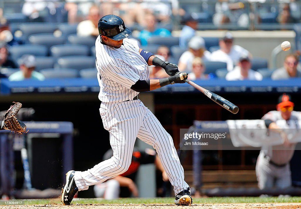 Eduardo Nunez #26 of the New York Yankees connects on a run scoring sacrifice fly against the Baltimore Orioles at Yankee Stadium on July 6, 2013 in the Bronx borough of New York City. The Yankees defeated the Orioles 5-4.