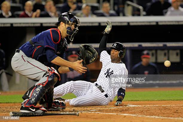 Eduardo Nunez of the New York Yankees slides in to home plate to score past Joe Mauer of the Minnesota Twins in the second inning on April 19 2012 at...