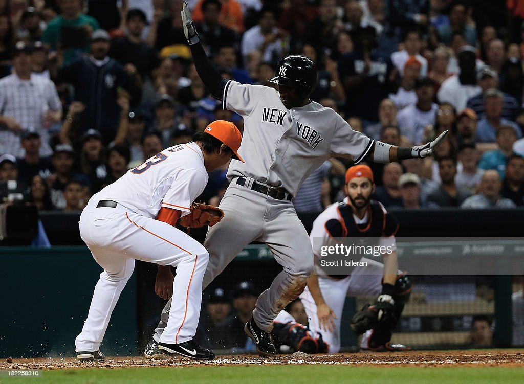 Eduardo Nunez #26 of the New York Yankees slides safe into home plate under the tag of Chia-Jen Lo #63 of the Houston Astros in the sixth inning at Minute Maid Park on September 28, 2013 in Houston, Texas.