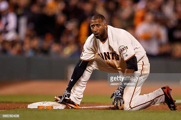 Eduardo Nunez of the San Francisco Giants kneels at third base after hitting a triple against the New York Mets during the fourth inning at ATT Park...