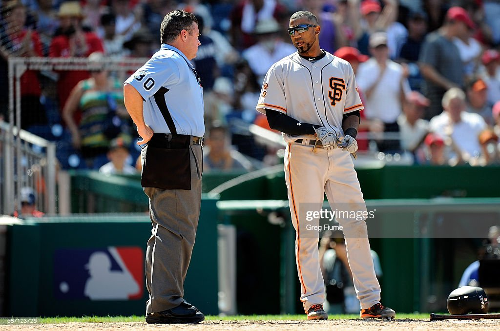 Eduardo Nunez of the San Francisco Giants talks with home plate umpire Rob Drake after being called out on strikes to end the eighth inning against...