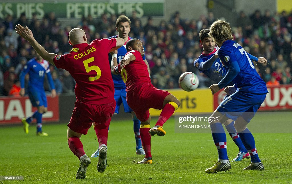 Eduardo of Croatia (2nd R) shoots past James Collins (L) and Ashley Williams of Wales (C) to score the winning goal during the FIFA 2014 World Cup qualifying football match between Wales and Croatia at Liberty Stadium in Swansea, south Wales, on March 26, 2013. Croatia won the game 2-1.