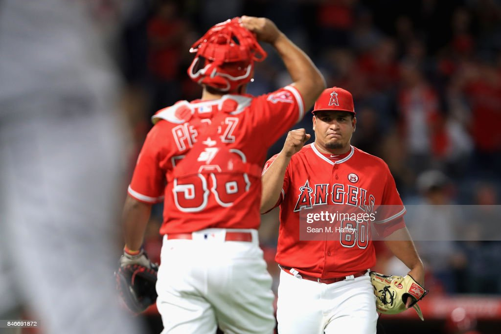 Eduardo Paredes #60 reacts with Carlos Perez #58 of the Los Angeles Angels of Anaheim after defeating the Houston Astros 9-1 in a game at Angel Stadium of Anaheim on September 13, 2017 in Anaheim, California.
