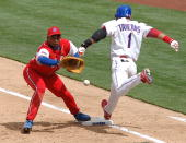 Eduardo Paret of Cuba awaits the relay as Willy Taveras of the Dominican Republic is safe on a bunt single in the SemiFinals of the 2006 World...