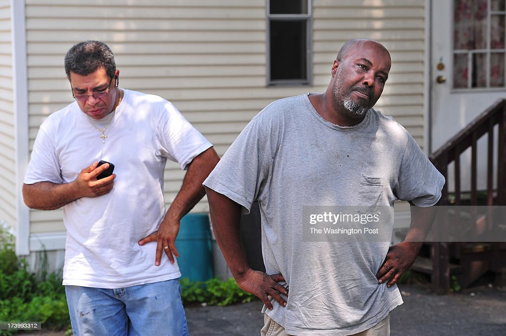 Eduardo Quinonez, left, and Thomas Watkins, right, stand not far from the scene of a crashed airplane in Parkway Village on Thursday July 18, 2013 in Laurel, MD. The plane damaged Watkins home before landing into Quinonez' home.