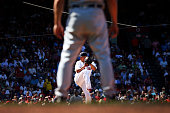 Eduardo Rodriguez of the Boston Red Sox delivers as seen thorugh the legs of Detroit Tigers first base coach Omar Vizquel in the sixth inning during...