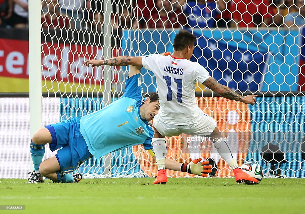 <a gi-track='captionPersonalityLinkClicked' href=/galleries/search?phrase=Eduardo+Vargas&family=editorial&specificpeople=1715151 ng-click='$event.stopPropagation()'>Eduardo Vargas</a> of Chile scores a goal beating goalkeeper <a gi-track='captionPersonalityLinkClicked' href=/galleries/search?phrase=Iker+Casillas&family=editorial&specificpeople=215446 ng-click='$event.stopPropagation()'>Iker Casillas</a> of Spain during the 2014 FIFA World Cup Brazil Group B match between Spain and Chile at Estadio Maracana on June 18, 2014 in Rio de Janeiro, Brazil.