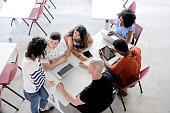 Grupo de pessoas se reunindo para aprender e ensinar, discutindo um assunto na reunião.