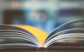 Open book on working desk in the library room with blurred focus for business and education background