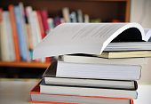 Stack of Education books on table in library, selective focus.
