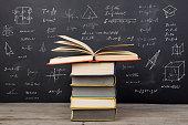 Education concept - books on the desk in the auditorium, formulas on the blackboard