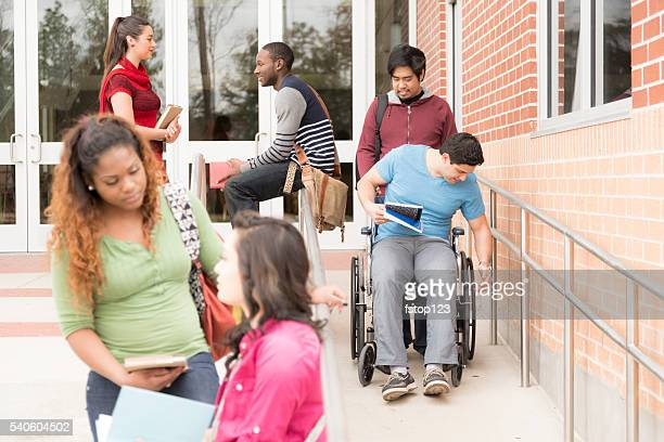 Education: Disabled student helped down wheelchair ramp. College campus.