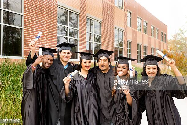 Educaton: Grande grupo de amigos de colégio entusiasmado depois de formatura. Diplomas.