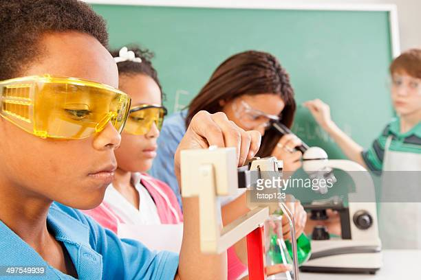 Education: Diverse students in chemistry class conducting an experiment.