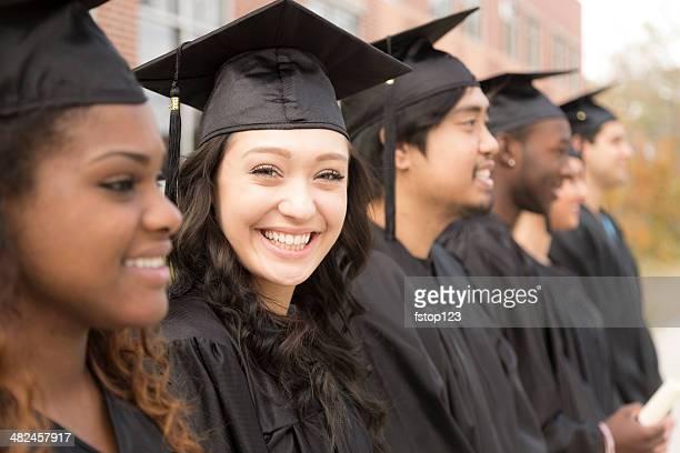 Éducation: Jeunes diplômés debout dans la rangée sur le campus universitaire.