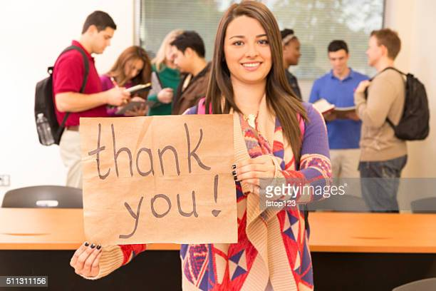 Education: Latin descent college student holds 'Thank you' sign. Classroom.