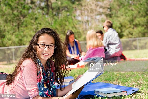Education: Latin pre-teenage girl studies at local park. Friends background.