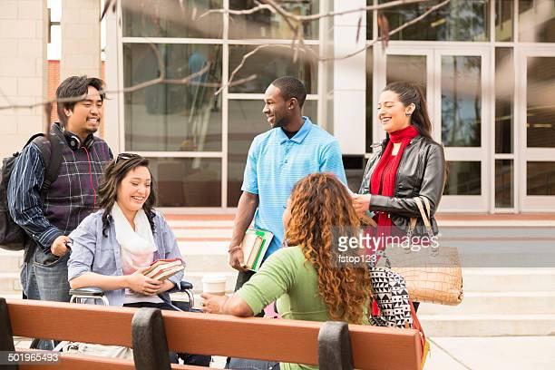 La educación: Multiétnico de la Universidad los estudiantes hablando en el campus.  Uno en silla de ruedas.