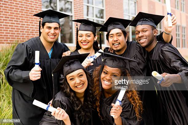 Education: Multi-ethnic friends excitedly hold diplomas after college graduation.