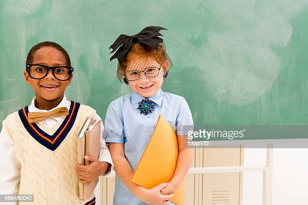 Education:  Retro-revival students in front of school chalkboard.