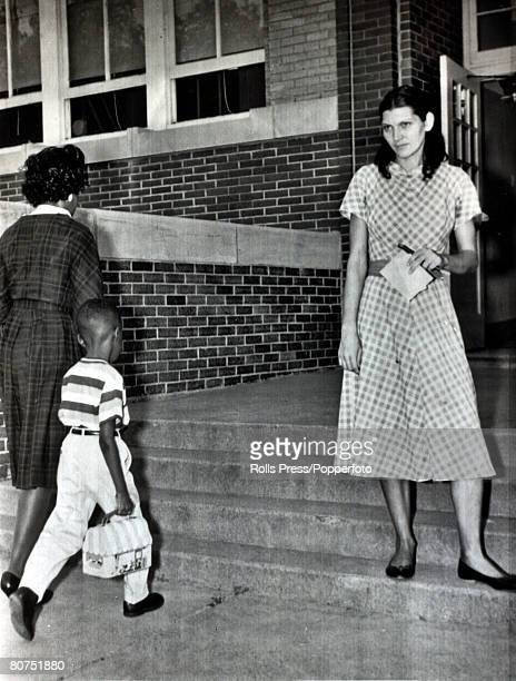6th September 1961 Dallas Texas A white woman watches stony faced as a black woman with her child walks past into an elementary school as integration...