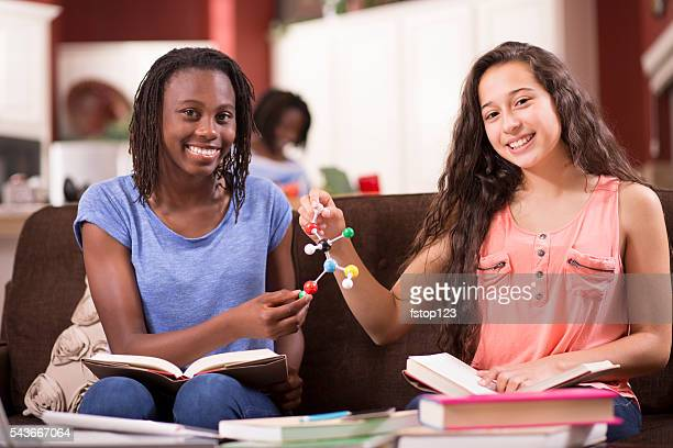 Education.  Teenage girls studying DNA molecule, science at home. Homework.